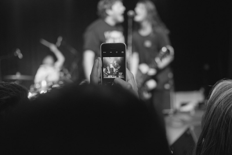 a person holding up a phone at a concert