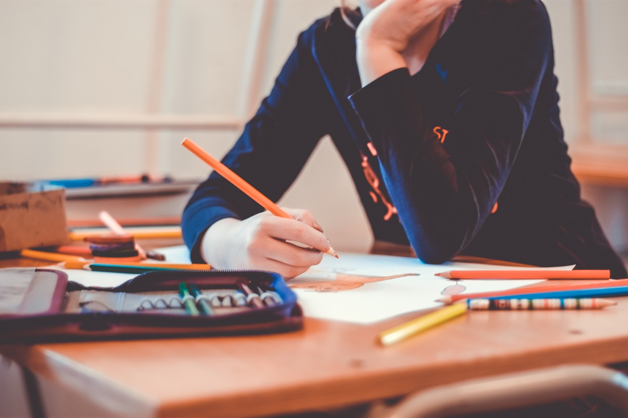 Student sitting at a desk coloring with a colored pencil.