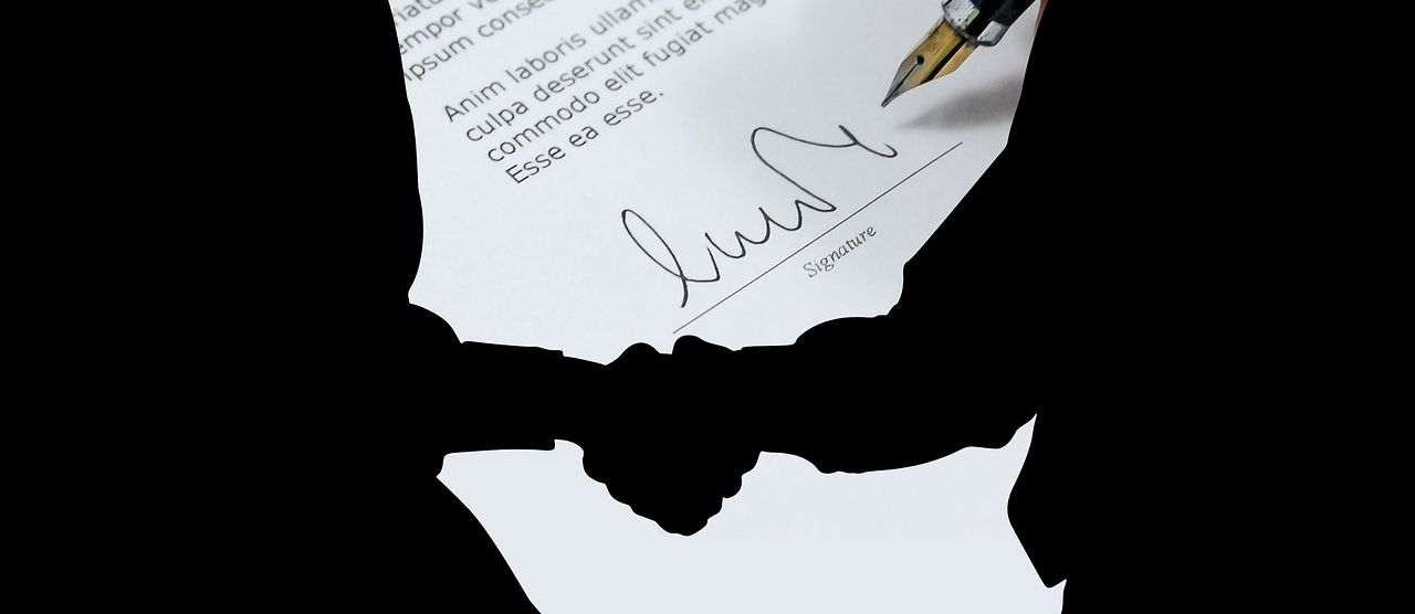 men shaking hands in front of signed contract